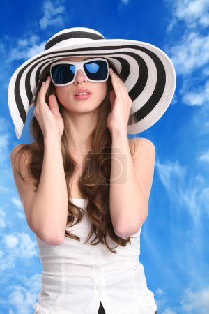 Photo for Beautiful woman in striped hat and sunglasses with hands near face on background of the blue sky - Royalty Free Image