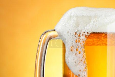 Photo pour Tasse à bière avec mousse sur fond jaune - image libre de droit