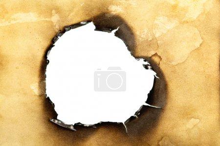 Photo pour Gros plan du trou brûlé dans du vieux papier jaune - image libre de droit