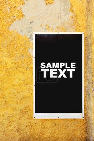 Photo pour Affiche sur mur jaune minable. Mettez votre propre texte ou image ici - image libre de droit
