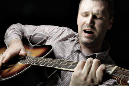 Photo for Man with acoustic guitar over black background - Royalty Free Image