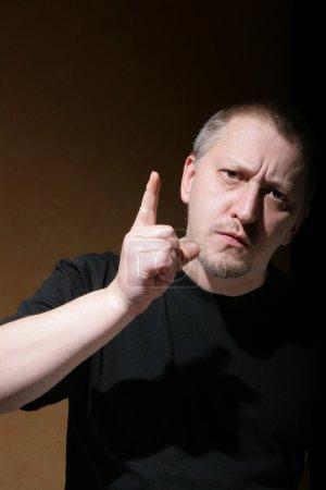 Photo pour L'homme secoue son pouce sur quelqu'un sur fond sombre - image libre de droit