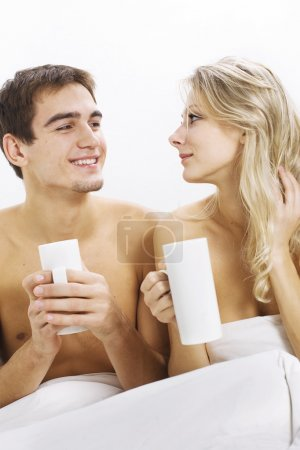Happy couple with coffee on the bed