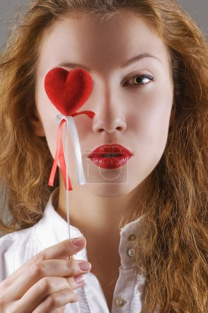Photo for Portrait of young beautiful woman holding red heart-shaped symbol - Royalty Free Image