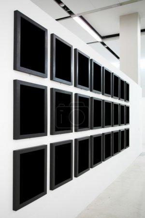 Photo pour Murs dans le musée avec cadres vides noirs - image libre de droit