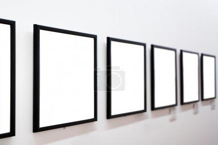 Photo pour Cadres vides sur mur blanc au musée - image libre de droit
