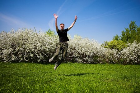 Photo for Active jumping man on green grass - Royalty Free Image