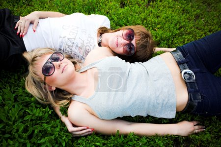 Two girls in sunglasses lays