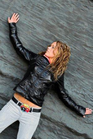 Photo pour Fille adolescente en noir séjour près du mur gris - image libre de droit