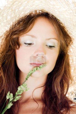 Sonriente chica en sombrero con hierba