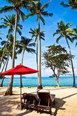 parapluie rouge et chaises sur la plage de sable