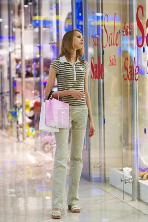 """Photo for Girl in shopping mall looking on a show-window with """"sale"""" written on it - Royalty Free Image"""