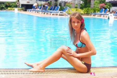Photo for Girl near tropical pool with flower in hairs - Royalty Free Image
