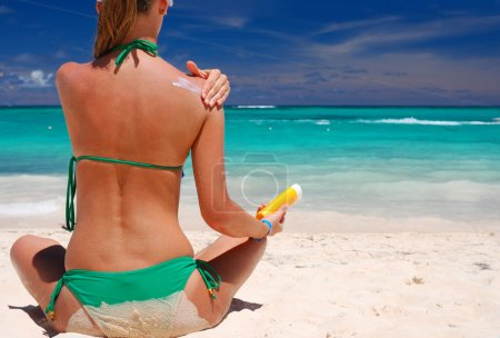 Photo for Tan woman applying sun protection lotion - Royalty Free Image