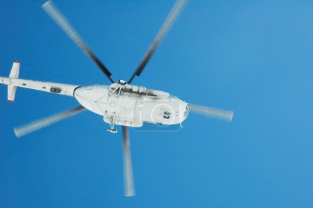 Flying helicopter against blue sky