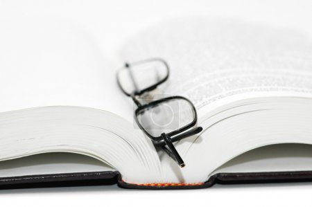 Photo for Reading glasses over the open textbook - shallow DOF - Royalty Free Image