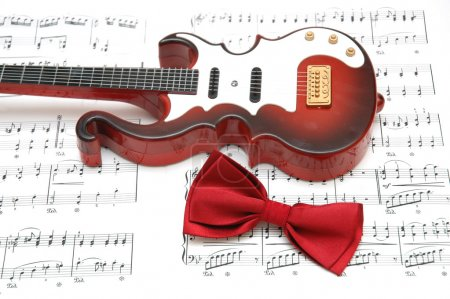 Guitar and bow tie over the sheet