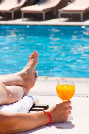 The woman at pool with a juice glass
