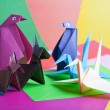 Origami. Figures of birds and animals against colo...