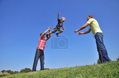 Photo for A father throwing his son in the air and catching him - Royalty Free Image