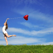 Girl with a red ball in the form of heart on the b...
