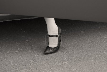 Female leg in a high heel shoe at a car