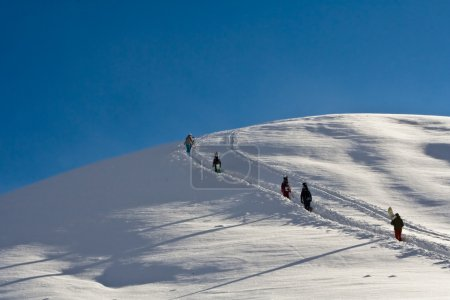Snowboarders walking up the mountain