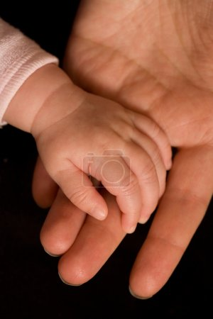 Photo pour Main de bébé dans la main adulte - image libre de droit