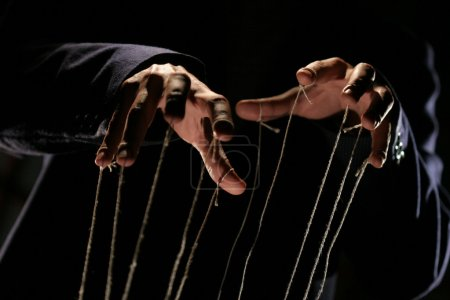 Photo for Conceptual series: hands of puppeteer with rope - Royalty Free Image