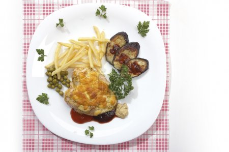 Photo for Appetizing dish: chicken fillet with green peas, fry potatoes and grilled aubergine - Royalty Free Image