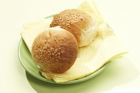 Photo for Two dinner roll with sesame on yhe green plate - Royalty Free Image