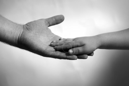 Photo for Child hand lying over man's adult palm - Royalty Free Image
