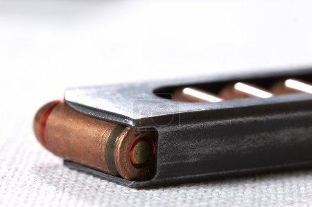 Photo pour Gros plan de la balle du pistolet sur le fond en tissu blanc - image libre de droit