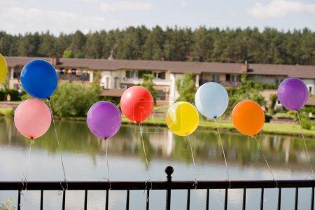 Helium baloons at bridge with lake and h