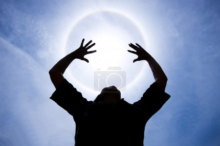 Person with hands up around Halo