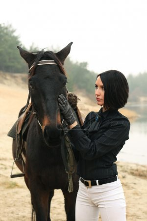 Beautiful woman with a horse near river