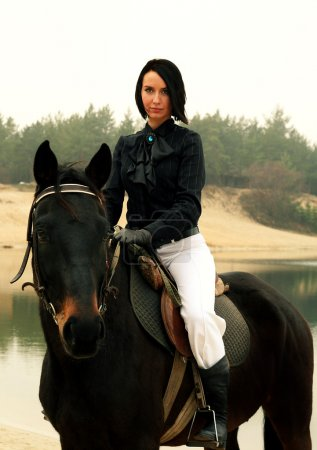 Beautiful elegant woman riding a horse