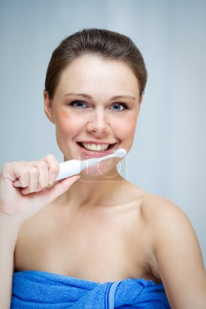 Woman cleaning her teeth by toothbrush