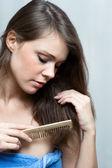 Atraktivní žena česání vlasy