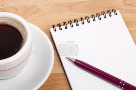 Taza de café expreso con bloc de notas en blanco y pluma