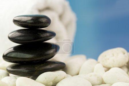 Photo pour Serviette blanche et pebbless sur fond bleu ciel - image libre de droit