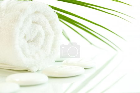 Photo for White pebbles, towel and palm leaf over white. Selective focus. - Royalty Free Image