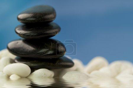 Photo pour Cailloux sur des pierres blanches sur fond bleu ciel reflété dans l'eau - image libre de droit
