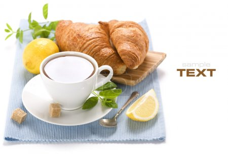 Photo for Herbal tea, mint, lemon and croissants on blue napkin (with sample text) - Royalty Free Image