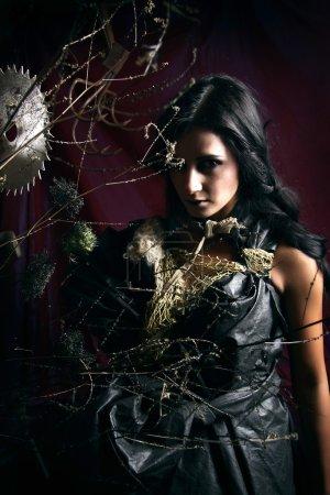 Photo pour Sorcière stylisée dans des buissons et des outils tranchants dangereux. photo d'Halloween. - image libre de droit