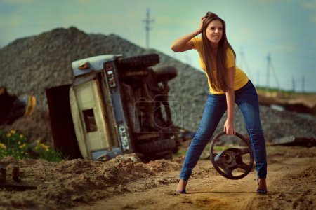 Photo for The girl with wheel in a hand against broken car. Photo. - Royalty Free Image