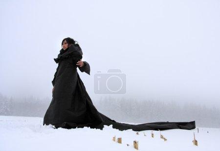 Photo pour Mystérieuse fille dans une longue robe noire sur la neige . - image libre de droit