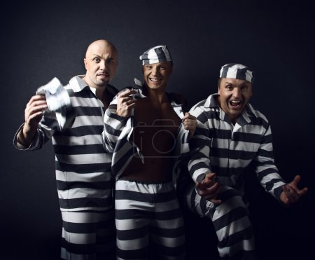 Photo for Three prisoners. Group of men in suits of convicts. - Royalty Free Image