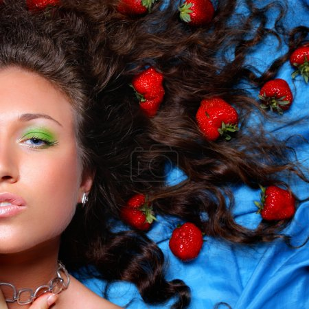 Portrait of beautiful woman with strawbarries in hair