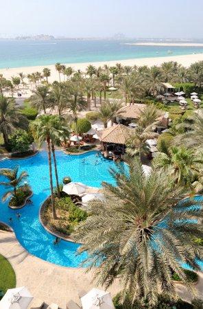 Photo pour Piscine à l'hôtel zone de loisirs, plage et vue sur l'île artificielle de Jumeirah Plam, Dubaï, Émirats arabes unis - image libre de droit
